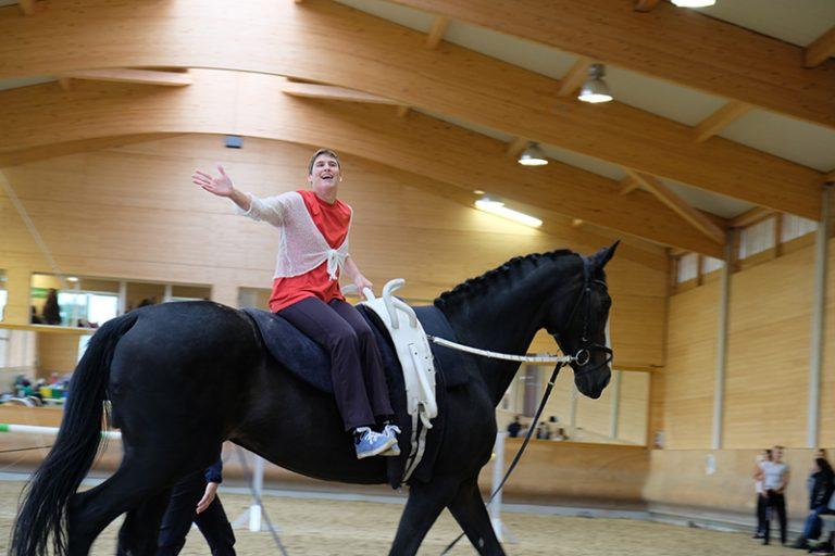 Auf einem großen schwarzem Pferd sitzt seitlich eine Person auf dem Pferd und hält den rechten Arm zur Seite und strahlt.