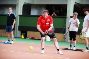 Im Mittelpunkt ein Tennisspielr im roten T-Shirt während des Spiels. Links und rechts hinter ihm stehen drei weitere SpielerInnen in Unschärfe bereit für ihren Einsatz.