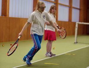 Zwei Mädchen stehen in der Tennishalle am Netz. Eine von ihnen im Vordergrund ist dabei den kommenden Ball anzunehmenm, während die andere wartet.