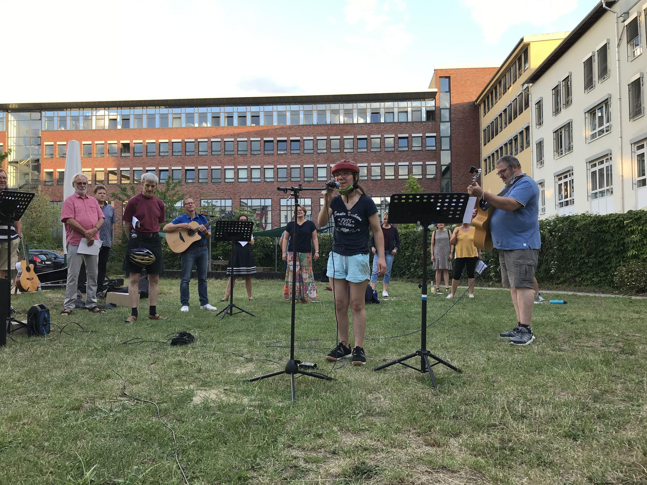 Sängerinnen und Sänger stehen mit Instrumenten, Mikrofonen und Notenständern mit Abstand im Garten vor einem großen Gebäude.