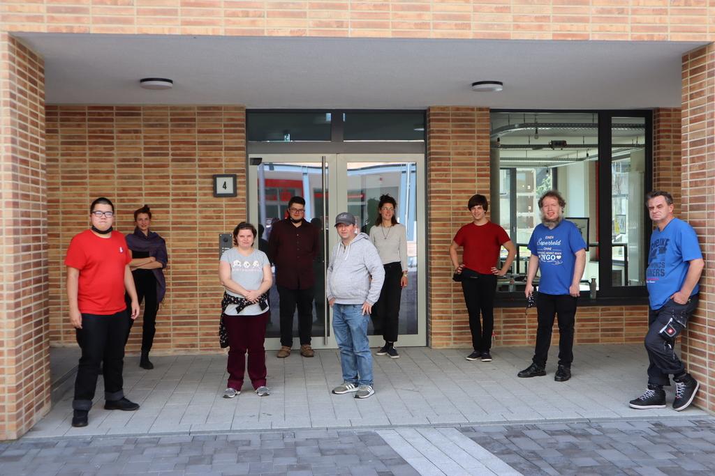 Vor dem Eingang des Kunsthauses stehem sieben von zehn angehenden Künstlern und Künstlerinnen. Sie halten den Mindestabstand ein, weswegen sie nicht nah beieinander stehen.