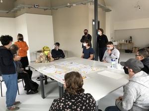 An einem großen Tisch in einem hellen Raum sitzen und stehen Personen die einen Mund-Nasen-Schutz tragen. Auf dem Tisch liegen viele Pläne.