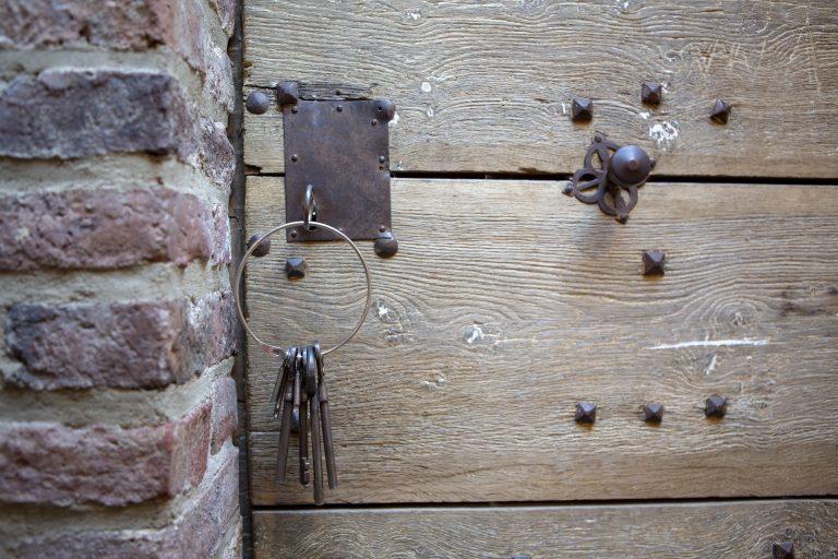 Ein Schlüssel steckt in demSchloss einer hölzernen, alten Tür an einer Mauer. An dem Schlüssel hängt ein großer, runder Schlüsselbund an dem weitere Schlüssel baumeln.