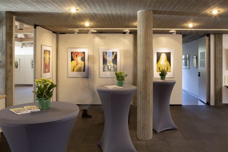 Drei Stehtische mit Husse auf denen jeweils eine Blume und Prospekte liegen, stehen in einem Raum in dem Bilder einer Ausstellungen an den Wänden hängen. Zwei offene Türen führen zu Nebenräumen.