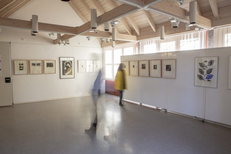 Blick in einen leeren Raum, in dem Bilder einer Ausstellung an den Wänden angebracht sind. Zwei verschwommene Menschen gehen durch den Raum.