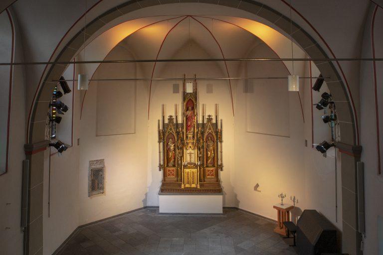Blick von oben auf den Altar in der Kirche Alt St. Ulrich. Auf der Erde steht ein Klavier dazu ein Hocker und Beistelltisch mit Kerzenständer.