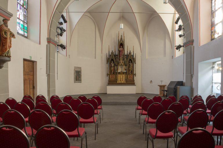 Blick von hinten auf den Altar über die Bestuhlung in der Kirche Alt St. Ulrich.