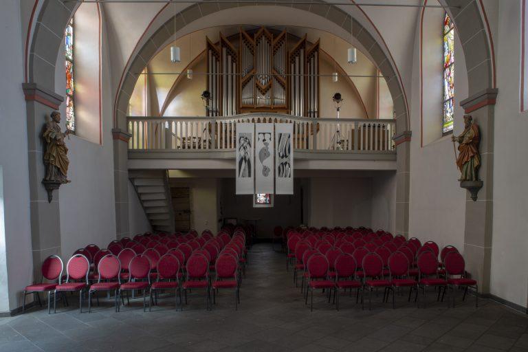 Blick von der Bühne aus auf die Bestuhlung und Empore mit Orgel in der Kirche Alt St. Ulrich.