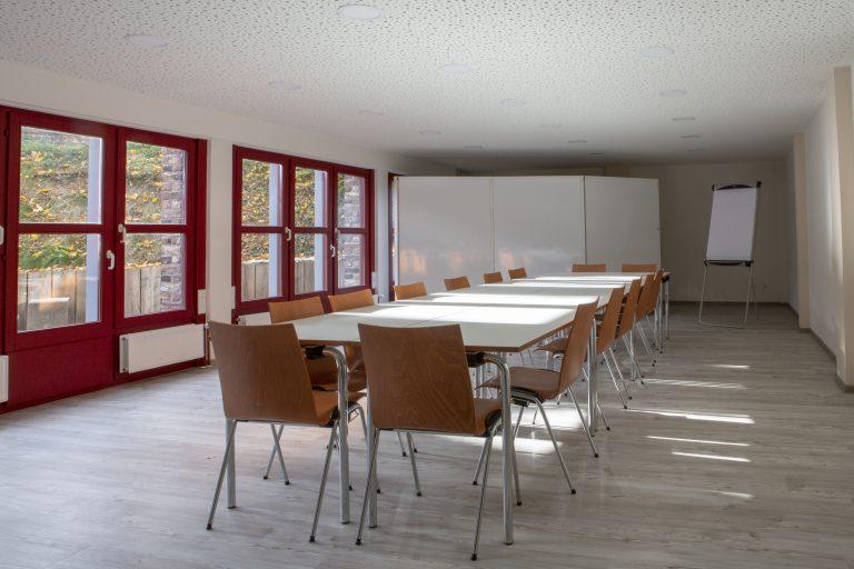 An einem großen weißen Tisch in einem Tagungsraum mit Fenstern stehen viele Stühle für circa 15 Leute.