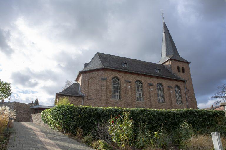 Hinter einer Hecke auf einer Erhöhung steht die Kirche Alt St. Ulrich. Im Hintergrund ist der bewölkte Himmel.