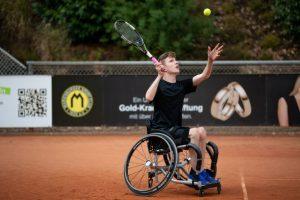 Ein junger Tennisspieler im Rollstuhl auf dem Tennisplatz ist dabei einen Aufschlag zu spielen.