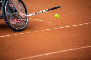Ein Spieler titscht mit seinem Schläger den Tennisball auf der Erde in die Höhe. Es sind nur ein Rad des Rollstuhls, der Schläger in der Hand des Spielers und der Ball zu sehen.
