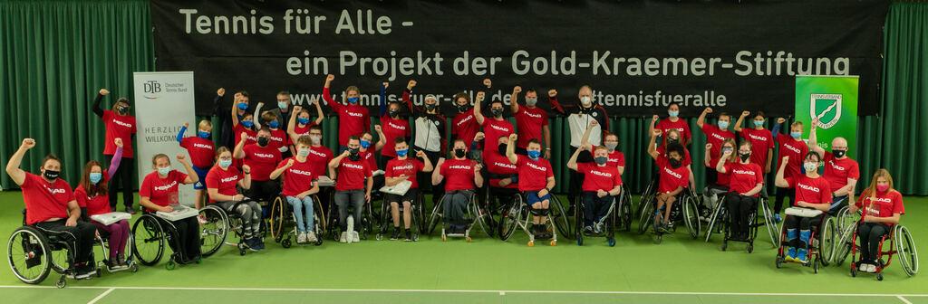 Die Teilnehmer*innen und Helfer*innen tragen alle ein rotes T-Schirt und bilden einen Gruppe fürs Foto vor einem großen Banner.