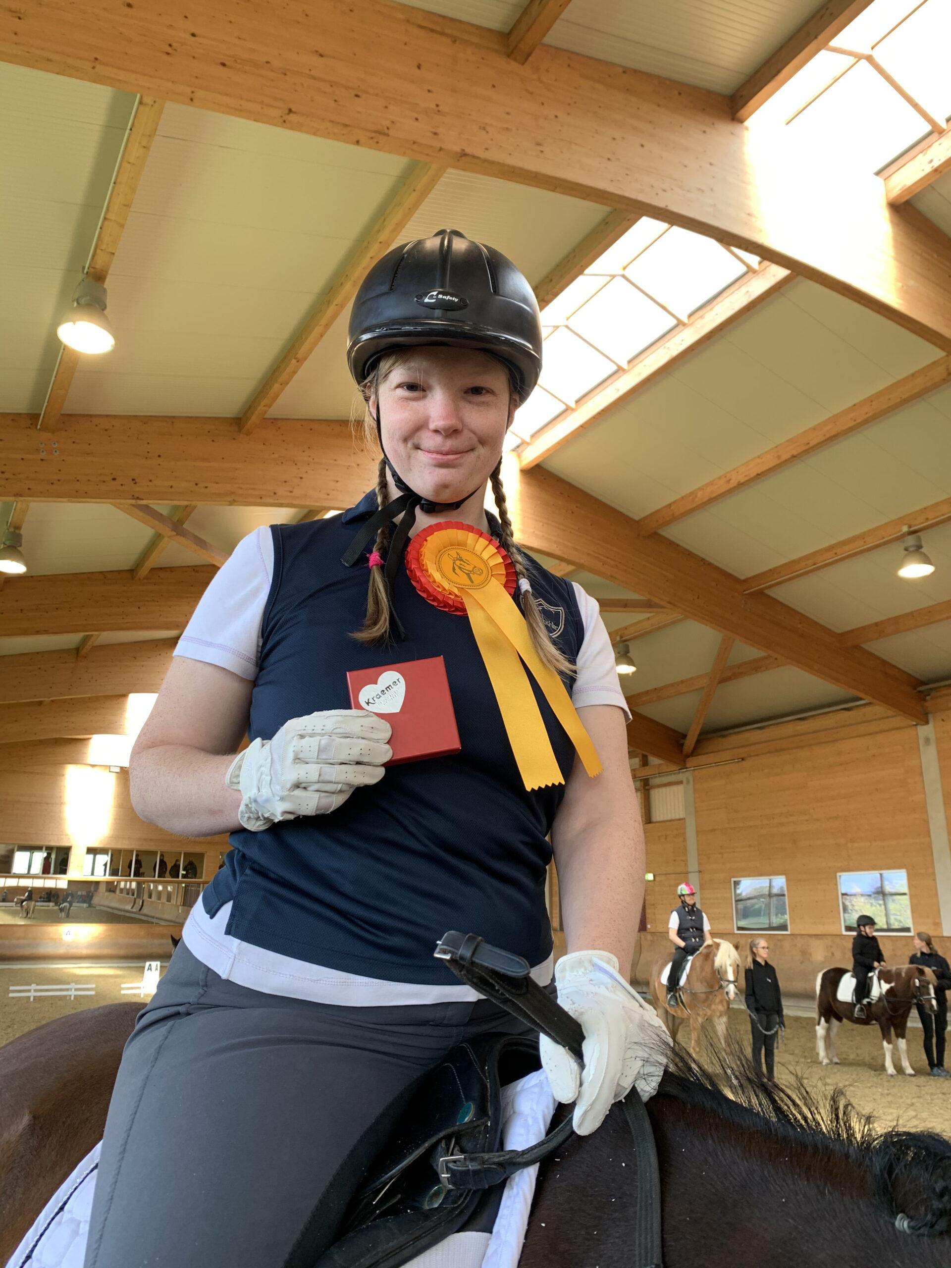 Eine junge Frau sitzt auf einem Pferd und hält einen Preis in ihrer Hand. An ihrem Polo hängt die Siegerschleife.