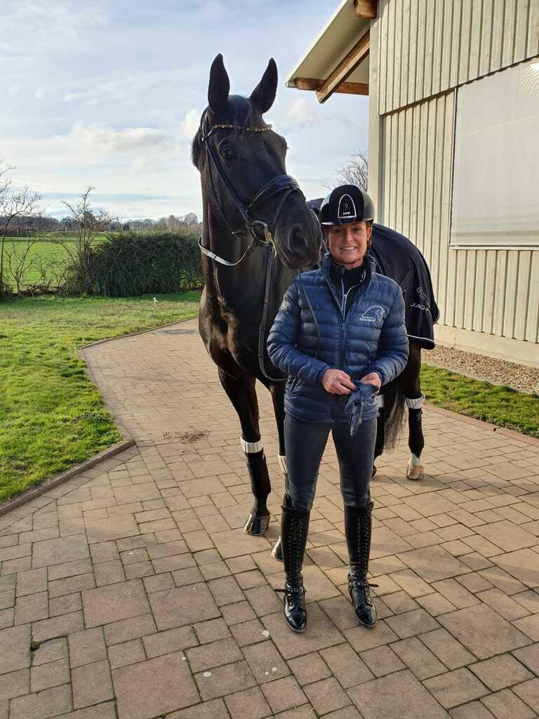 Vor der Reithalle steht eine Reiterin neben ihrem schwarzen Pferd.