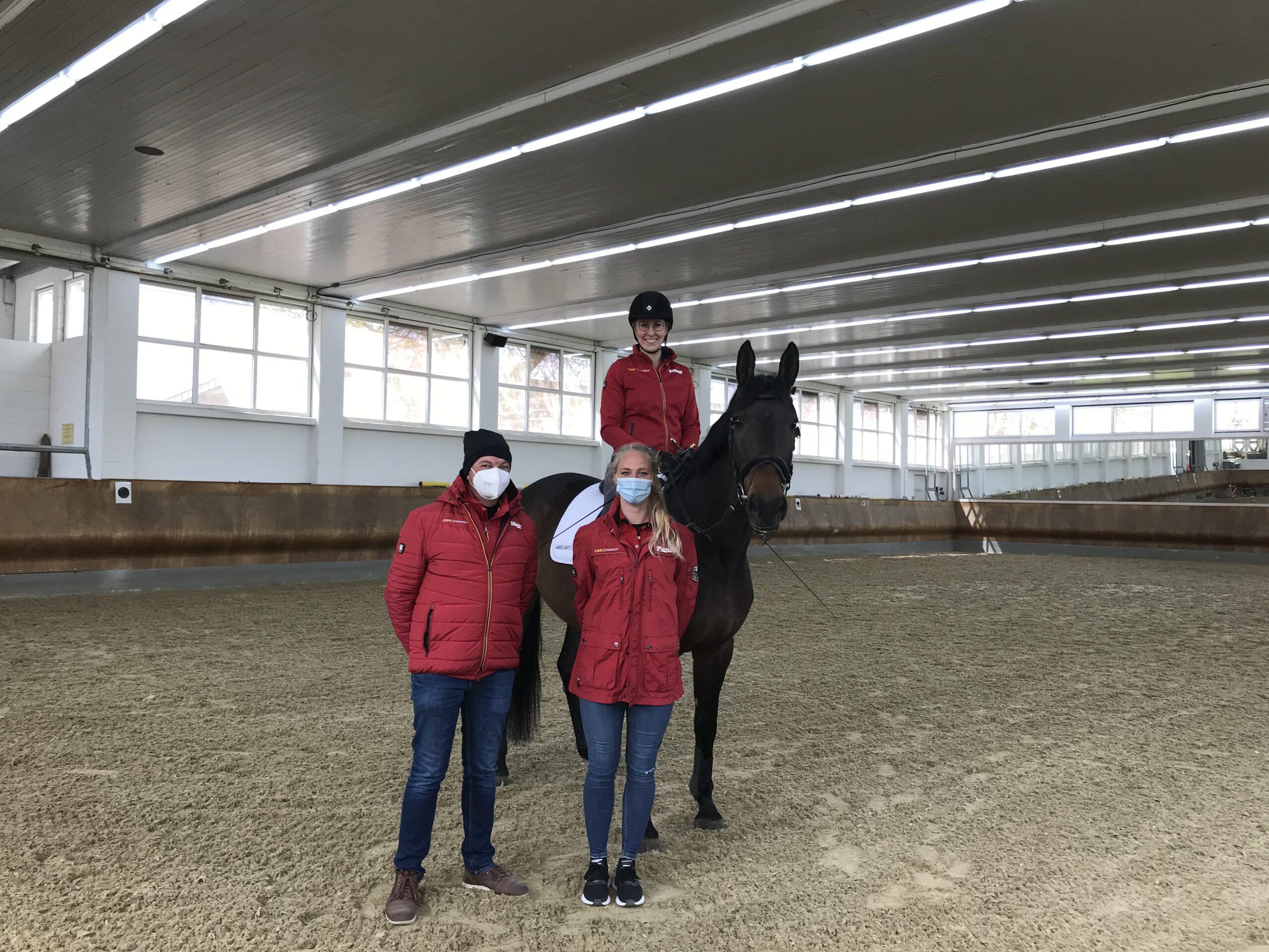 Vor einem Pferd mit Reiterin stehen zwei Personen. Alle drei tragen eine rote Jacke. Sie befinden sich in einer Reithalle.