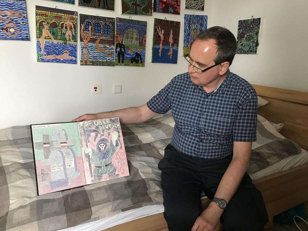 Auf dem Bild sitzt ein Künstler auf einem Bett. In der rechten Hand hält er ein Kunstwerk Im Hintergrund hängen mehrer Bilder an der Wand.