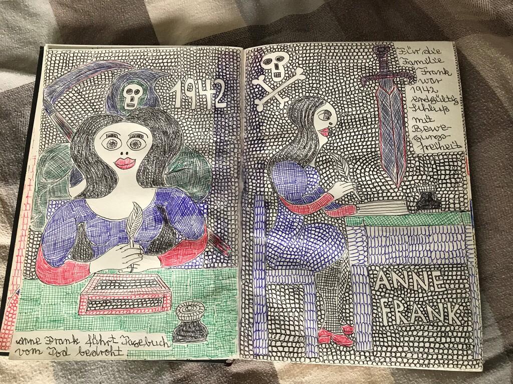 Auf einem Bett liegt eine Malerei von Anne Frank, wie sie am Schreibtisch sitzt und Tagebuch schreibt.