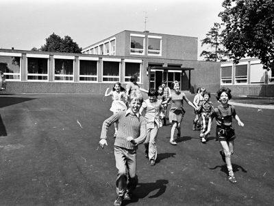 Kinder laufen aus der Schule über den Pausenhof.